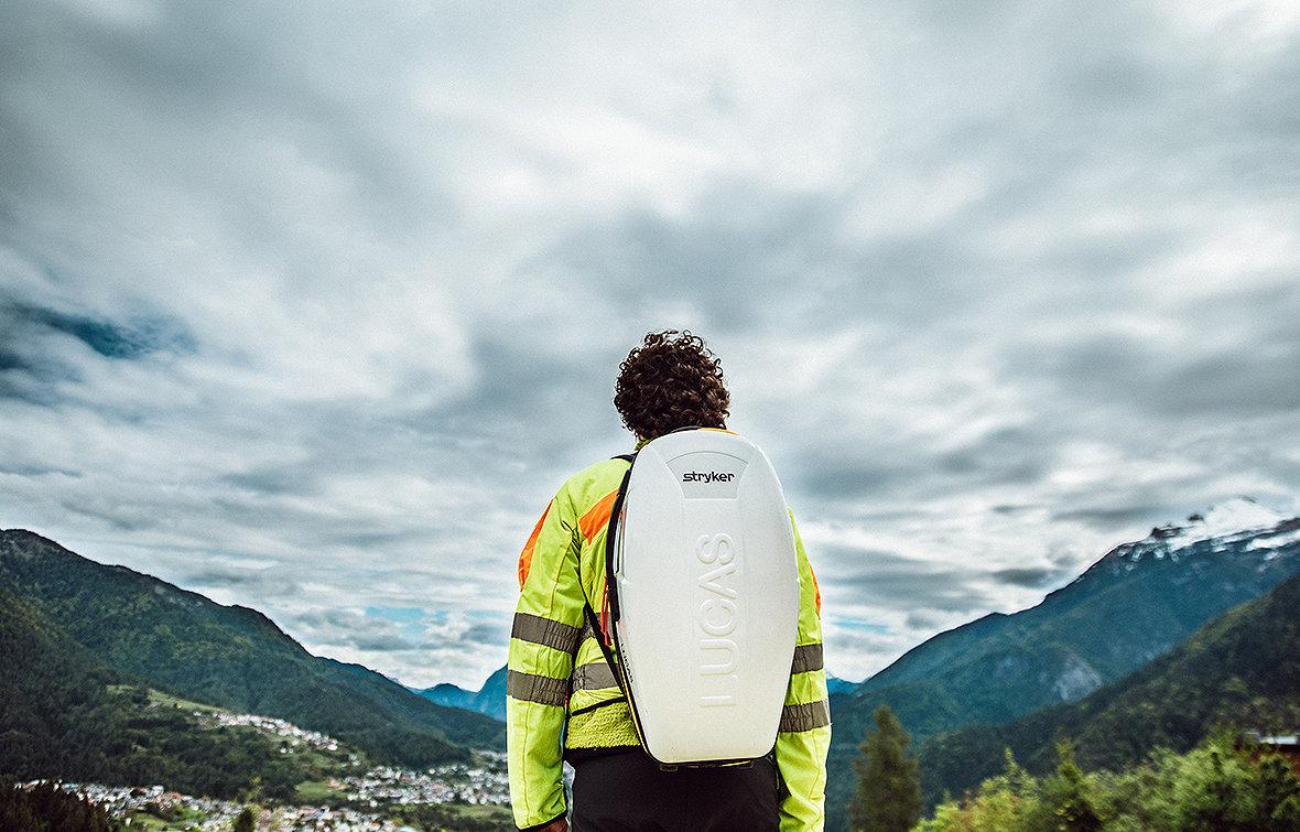 Ratownik medyczny niosący system kompresji klatki piersiowej LUCAS 3 w plecaku na plecach