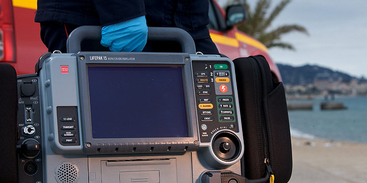Работник скорой медицинской помощи несет в руке монитор/дефибриллятор LIFEPAK 15