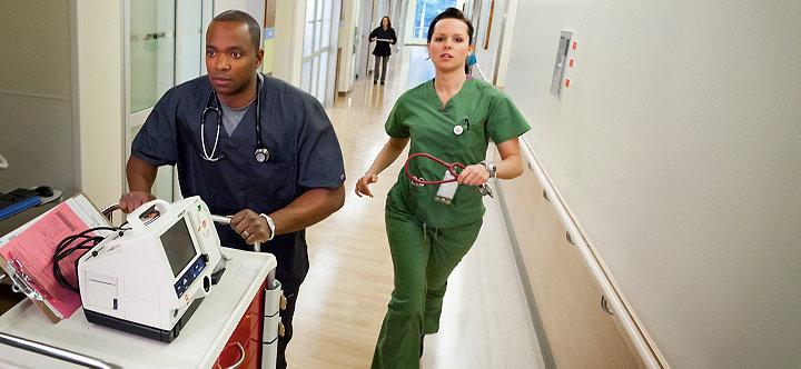 Pracownicy opieki zdrowotnej biegnący szpitalnym korytarzem zdefibrylatorem/monitorem LIFEPAK20e na wózku