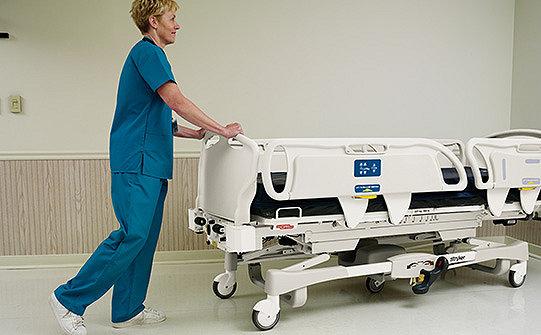 Caregiver pushing Stryker's GoBed II MedSurg Bed