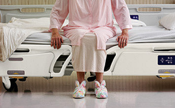 Patient sitting on Stryker's GoBed II MedSurg Bed, with the bed positioned at its low height