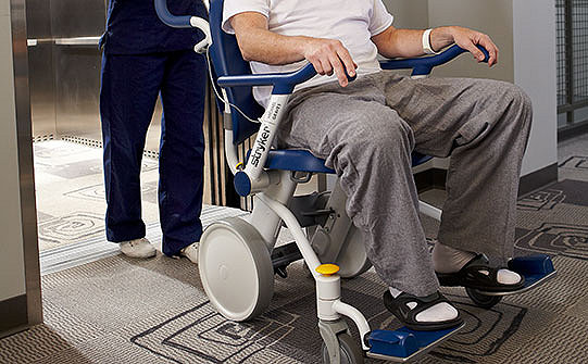 Caregiver pushing patient in Stryker's Prime TC Transport Chair