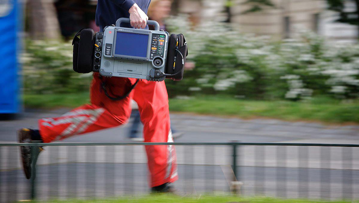 Работник скорой медицинской помощи спешит, неся в руке монитор/дефибриллятор LIFEPAK 15