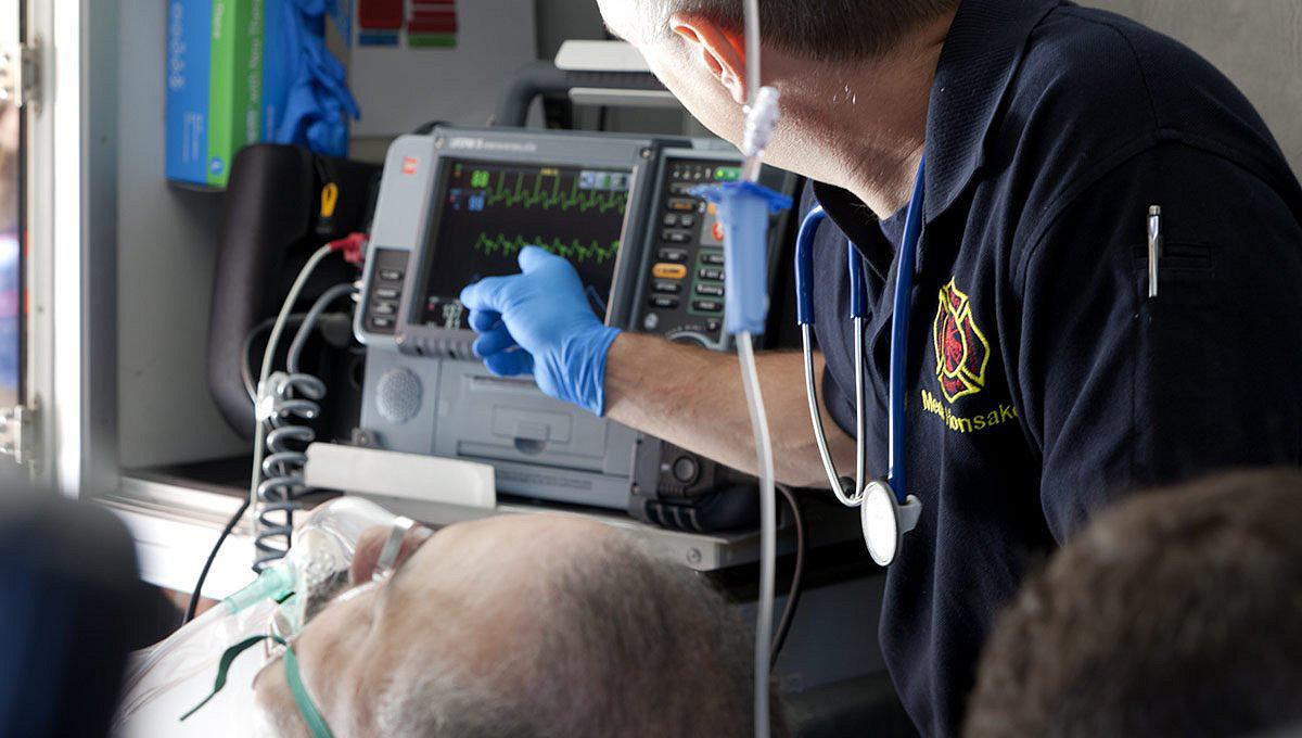 Указывающий жест на монитор/дефибриллятор LIFEPAK 15 работником скорой медицинской помощи в машине скорой помощи (увеличенное изображение)