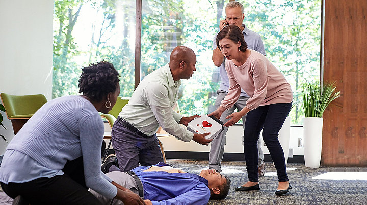 Umstehende halten den LIFEPAK CR2-Defibrillator und helfen dem am Boden liegenden Mann