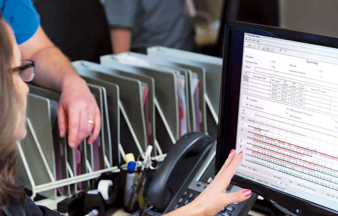 Profesional de servicios de emergencias observando datos de rendimiento en el software de revisión de datos CODE-STAT de Stryker